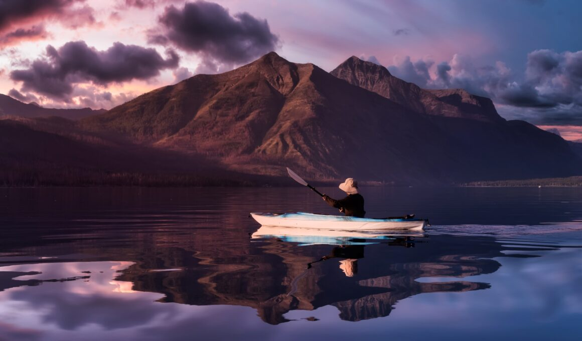 Kayaking in Lake McDonald with American Rocky Mountains in Background